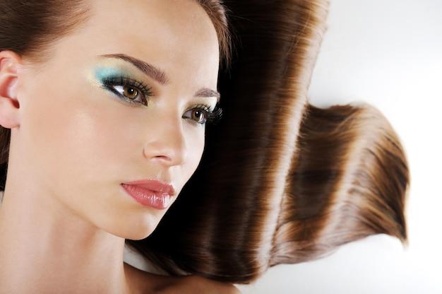 Piękna twarz kobiety z brązowymi długimi zdrowymi włosami