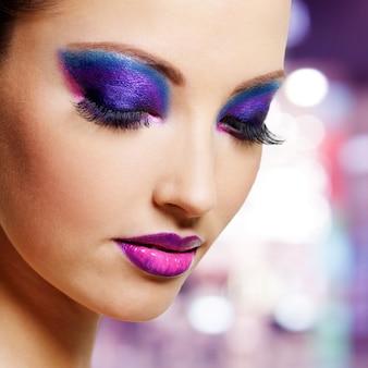 Piękna twarz kobiety z jasny fioletowy makijaż moda