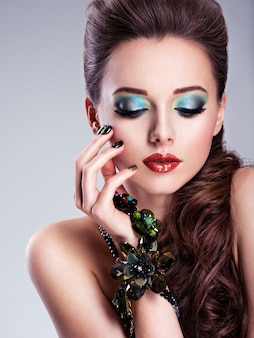 Piękna twarz kobiety z moda zielony makijaż i biżuterię pod ręką
