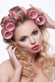 Piękna twarz kobiety z pięknym makijażem i lokówki we włosach.