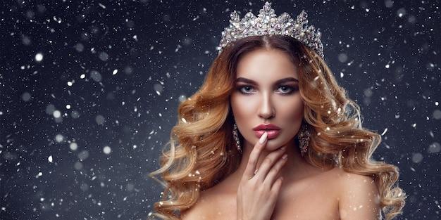 Piękna twarz kobiety z pięknymi kolorami makijażu. wizerunek królowej. ciemne włosy, korona na głowie, czysta skóra, piękna twarz, pulchne usta.
