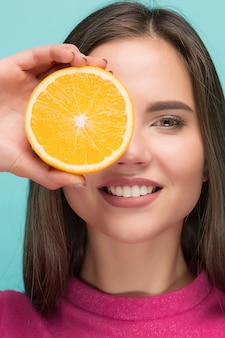 Piękna twarz kobiety z soczystą pomarańczą