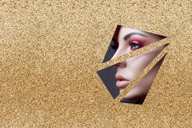 Piękna twarz makijaż czerwonych oczu młodej dziewczyny w szczelinie z żółtego złota papieru. kobieta z pięknym makijażem czerwonym świecącym cieniem, pulchne usta, duże oczy w złotej szczelinie