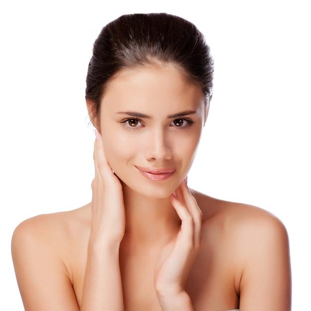Piękna twarz młoda dorosła kobieta z czystą świeżą skórą - odizolowywającą na bielu