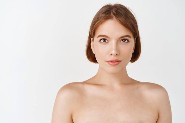 Piękna twarz. młoda dziewczyna z gołymi ramionami i naturalny makijaż twarzy patrzeć. kobieta o czystej, świeżej skórze, kosmetyki do pielęgnacji skóry po efekcie, biała ściana