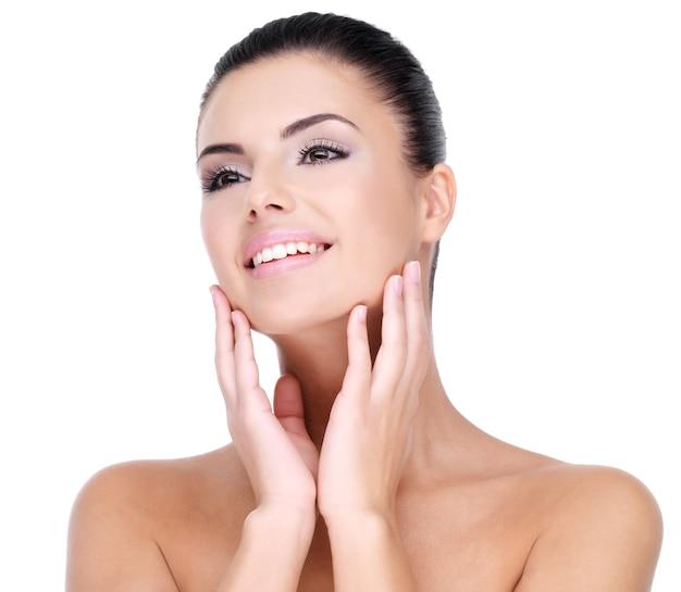 Piękna twarz młodej kobiety uśmiechnięte z czystą, świeżą skórą - na białym tle