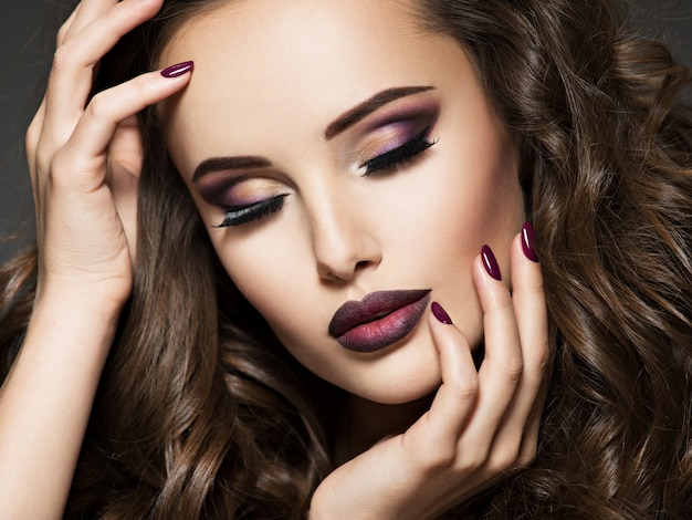 Piękna twarz młodej kobiety z bordowym makijażem. portret pięknej dziewczyny z winnymi ustami