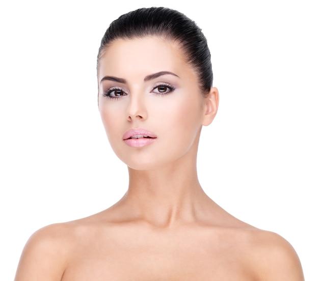 Piękna twarz młodej kobiety z czystą, świeżą skórą - na białym tle