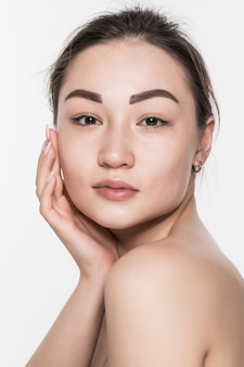 Piękna twarz młodej kobiety z czystą świeżą skórą odizolowywającą na biel ścianie. koncepcja pielęgnacji skóry i ciała.