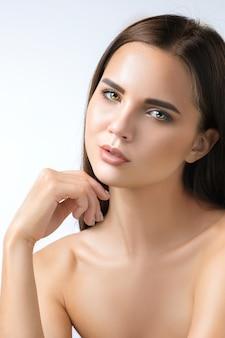 Piękna twarz młodej kobiety z czystą, świeżą skórę z bliska na białym tle.