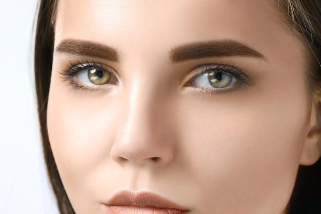 Piękna twarz młodej kobiety z czystego, świeżego skóry z bliska na białym tle.