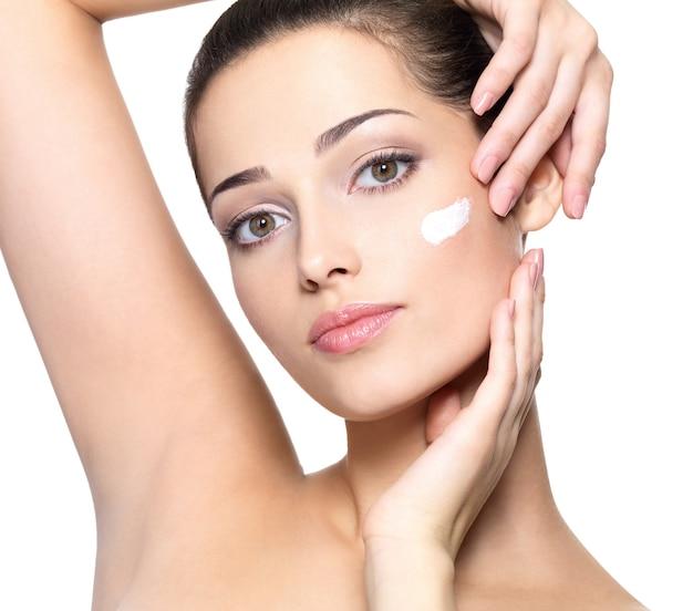 Piękna twarz młodej kobiety z kosmetycznym kremem na policzku. koncepcja pielęgnacji skóry.