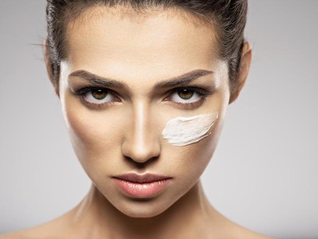 Piękna twarz młodej kobiety z kosmetycznym rozmazem kremu na twarzy w pobliżu oka. koncepcja pielęgnacji skóry. koncepcja zabiegów kosmetycznych.