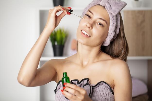 Piękna twarz młodej kobiety z kremem kosmetycznym na policzku.