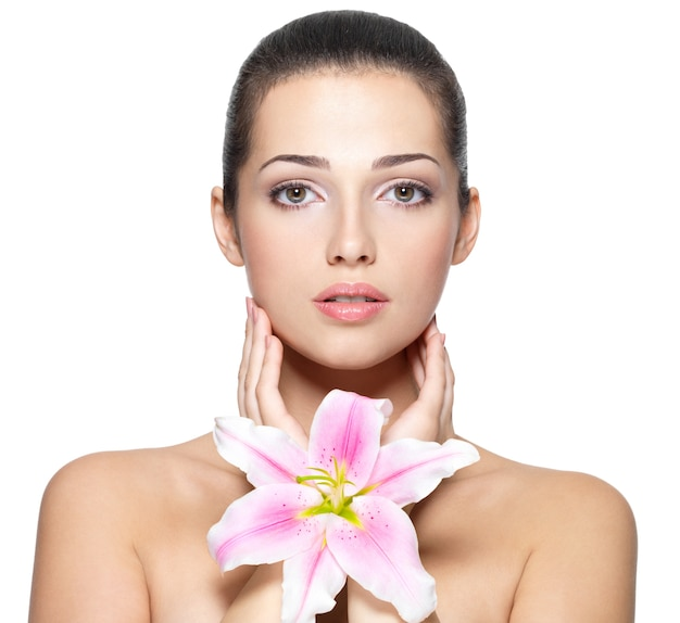 Piękna twarz młodej kobiety z kwiatem. koncepcja zabiegów kosmetycznych. portret na białej ścianie
