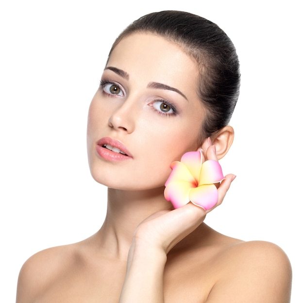 Piękna twarz młodej kobiety z kwiatem. koncepcja zabiegów kosmetycznych.
