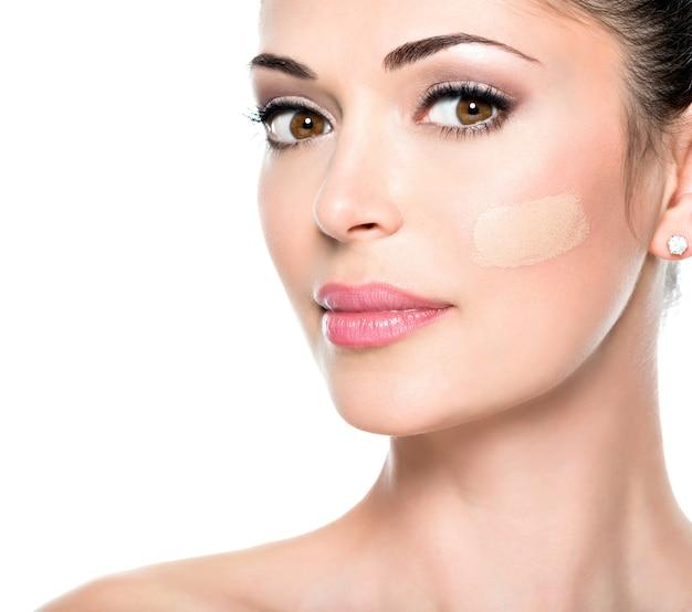 Piękna twarz młodej kobiety z podkładem kosmetycznym na skórze.
