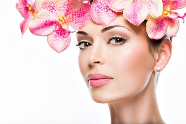 Piękna twarz młodej ładnej kobiety ze zdrową skórą i różowe kwiaty - na białym tle