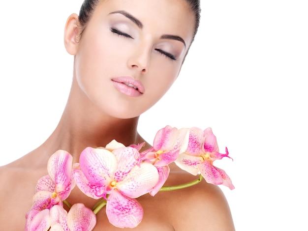 Piękna twarz młodej ładnej kobiety ze zdrową skórą i różowe kwiaty na ciele - na białym tle