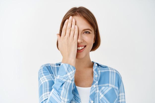 Piękna twarz. portret młodej kobiety zakrywającej pół twarzy i uśmiechniętej, przed i po efekcie pielęgnacji skóry, przy użyciu kremu do twarzy lub balsamu, stojąc na białej ścianie