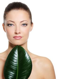 Piękna twarz świeżej kobiety z dużym zielonym liściem - na białym tle