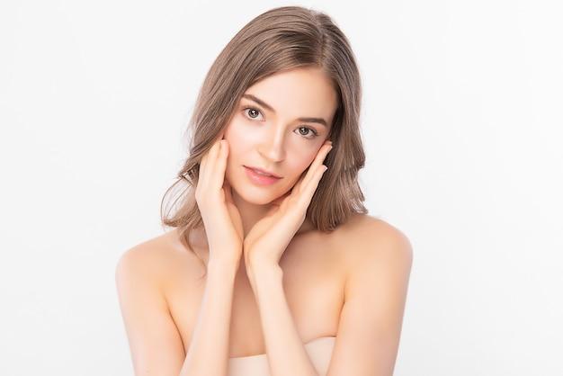 Piękna twarz. uśmiechnięta azjatycka kobieta dotyka portret zdrowej skóry. piękna szczęśliwa modelka ze świeżą, świecącą nawilżoną skórą twarzy i naturalnym makijażem