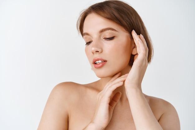 Piękna twarz. uśmiechnięta kobieta dotyka portret zdrowej skóry. piękna szczęśliwa dziewczyna model ze świeżą świecącą nawilżoną skórą twarzy i naturalnym makijażem na białej ścianie. koncepcja pielęgnacji skóry