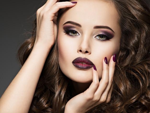 Piękna twarz zmysłowej kobiety z stylowym bordowym makijażem. wspaniała dziewczyna o seksownych oczach.