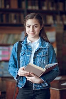 Piękna uczennica czytająca książkę w bibliotece, edukacja