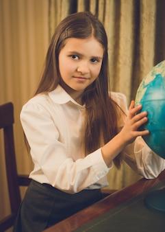 Piękna uczennica pozuje przy szafce z kulą ziemską