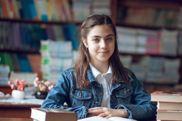 Piękna uczennica siedzi w bibliotece i czyta książkę, edukacja