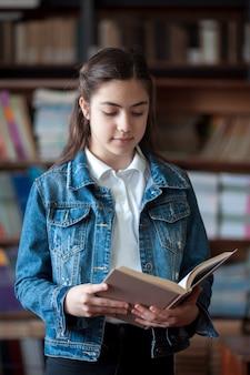Piękna uczennica stojąca w bibliotece i czytająca książkę, edukacja