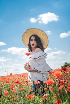 Piękna ukraińska dama sama w słomkowym kapeluszu na polu kwiatów maków, seksowny, słoneczny dzień
