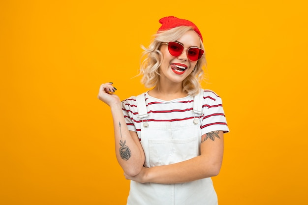 Piękna urocza blond dziewczyna z tatuażami na ramionach, ubrana w zimową czerwoną czapkę, t-shirt w paski i okulary przeciwsłoneczne na żółtym tle.
