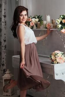 Piękna urocza brunetka w domu przy starym fortepianie, na którym leżały bukiety róż. mnóstwo świec na fortepianie. druhna na weselu. seksowna pani w ładnej spódnicy i bluzce