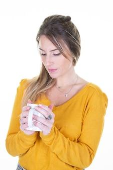 Piękna urocza dziewczyna z filiżanka kubkiem herbaciana kawa na bielu