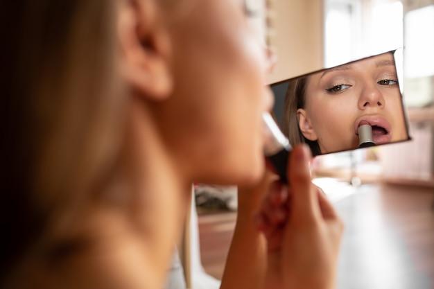 Piękna, urocza kobieta maluje szminkę szminką i patrzy w lustro w swojej sypialni