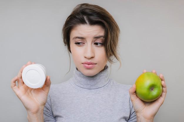 Piękna urocza młoda dama w bluzce przedstawiającej świeże zielone jabłko i puszkę kremu na szaro