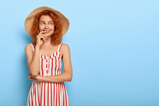 Piękna urocza młoda dama z rudymi włosami, pozowanie w letniej sukience i słomkowym kapeluszu