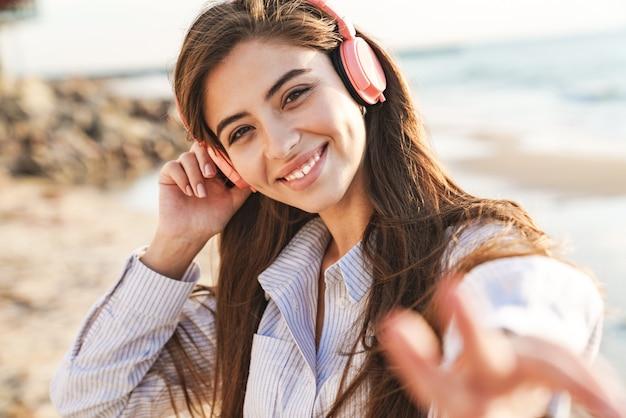 Piękna urocza młoda kobieta w letnich ubraniach spędzająca czas na plaży, słuchająca muzyki przez bezprzewodowe słuchawki