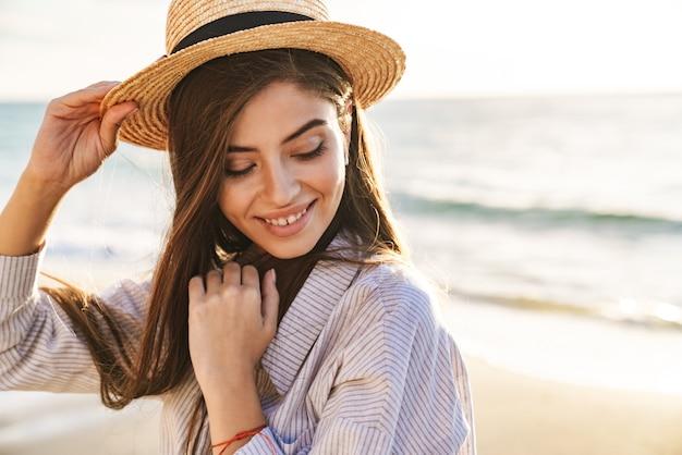 Piękna urocza młoda kobieta w letnich ubraniach spędzająca czas na plaży