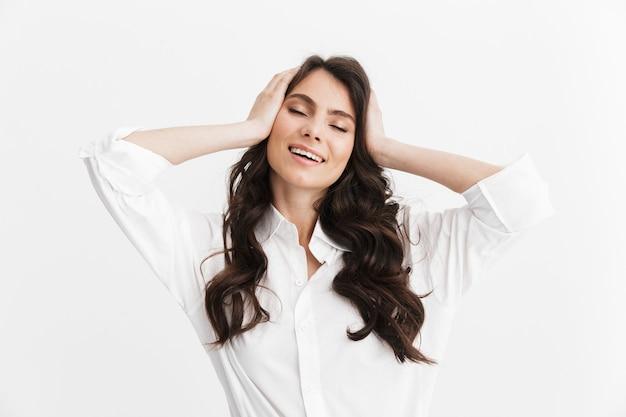 Piękna urocza młoda kobieta z długimi kręconymi włosami brunetki, ubrana w białą koszulę stojącą na białym tle nad białą ścianą