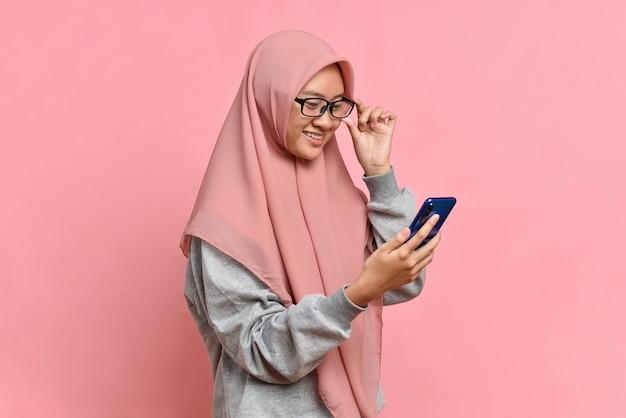 Piękna, urocza młoda muzułmańska kobieta wygląda na smartfona czytaj wiadomość na białym tle na różowym tle