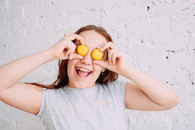 Piękna urocza rudzielec uśmiechnięta szczęśliwa nastolatek dziewczyna zamyka jej oczy macarons