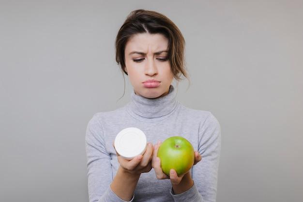 Piękna urocza zamyślona młoda dama w bluzce, trzymając i patrząc na świeże zielone jabłko i puszkę śmietany na szaro