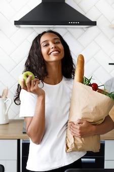 Piękna uśmiechana oliwkowa kobieta trzyma w jednej ręce paczkę z jedzeniem i jabłkiem w nowoczesnej białej kuchni
