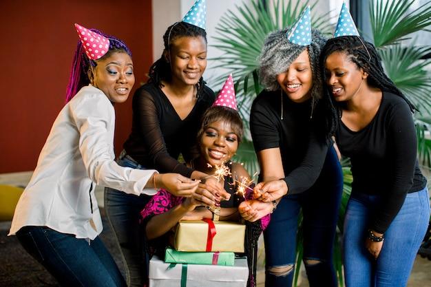 Piękna uśmiechnięta afrykańska dziewczyna trzyma prezenty w dłoniach i świętuje urodziny z przyjaciółmi. dziewczyny trzymają w dłoniach lampy bengalskie