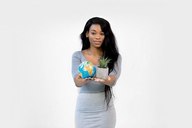 Piękna uśmiechnięta afrykańska kobieta pokazuje planety ziemi kulę ziemską i sukulent w garnku w rękach