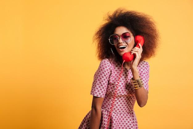 Piękna uśmiechnięta afrykańska kobieta w sukni pozuje z retro telefonem