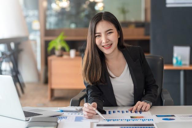 Piękna, uśmiechnięta azjatycka bizneswoman pracująca, wskazując na wykresie w biurze